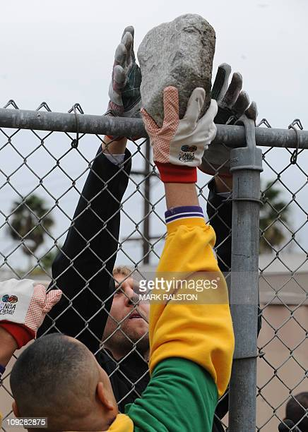 NBA star Dirk Nowitzki from the Dallas Mavericks passes a rock as he participates in the City Year School Refurbishment Project at the Virgil Middle...