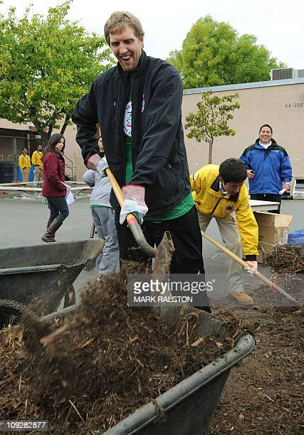NBA star Dirk Nowitzki from the Dallas Mavericks shovels mulch as he participates in the City Year School Refurbishment Project at the Virgil Middle...