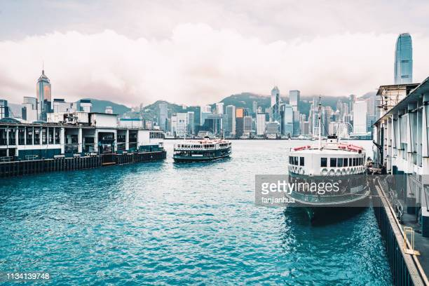 star ferries crossing the victoria harbor between the tsim sha tsui pier and hong kong island central in hong kong - star ferry stock pictures, royalty-free photos & images
