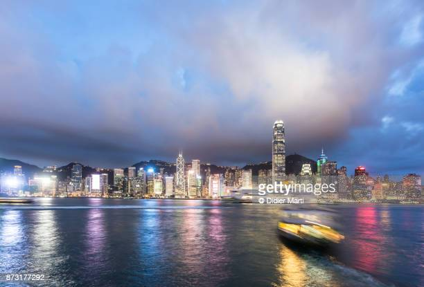 star ferry and other boat captured with blurred motion are crossing the victoria harbor in hong kong - didier marti stock photos and pictures