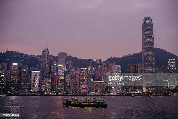 A Star Ferry Co vessel owned by Wharf Holdings Ltd sails across Victoria Harbor past Two International Finance Centre right and other buildings...