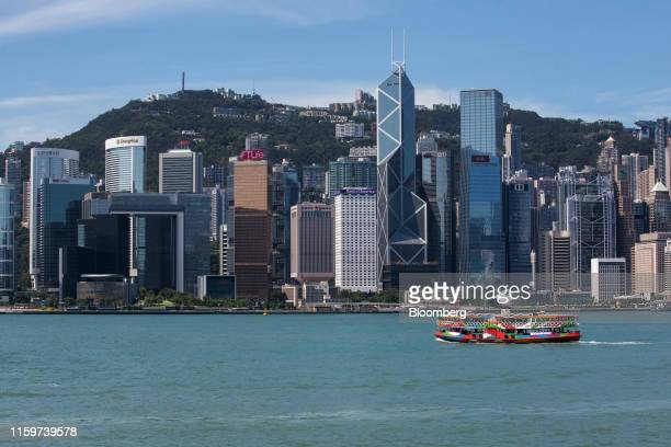 Star Ferry Co. Vessel, owned by Wharf Holdings Ltd., sails across Victoria Harbour in front of the Hong Kong island skyline in Hong Kong, China, on...