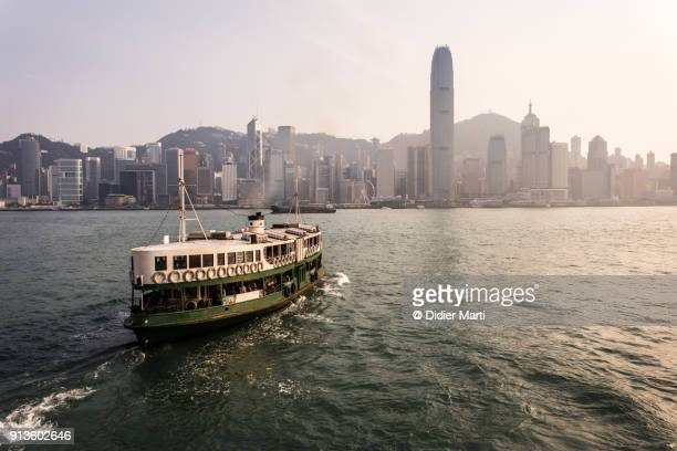 a star ferry leaving its tsim sha tsui pier in kowloon to reach the central pier in hong kong island at sunset - ferry photos et images de collection