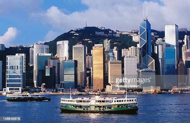 star ferry on victoria harbour with hong kong skyline (central) in background. - star ferry stock pictures, royalty-free photos & images