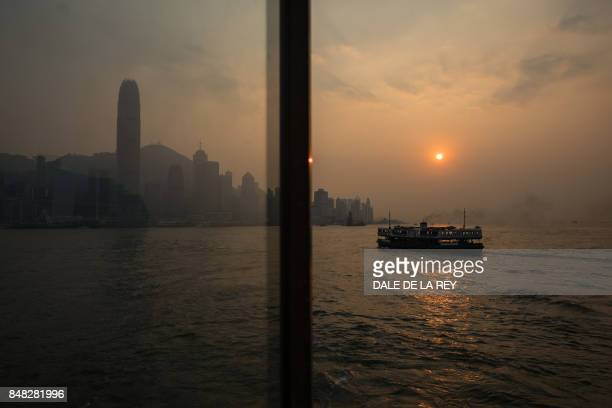 Star Ferry transports passengers across Victoria Harbour as the sun sets in Hong Kong on September 17 2017 / AFP PHOTO / DALE DE LA REY