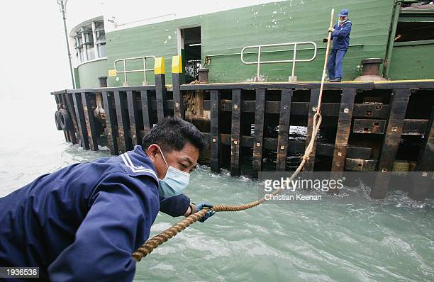Star Ferry worker pulls a rope as the boat docks at Hong Kong harbour April 17 2003 in Hong Kong Hong Kong's famous Star Ferry has seen a reduction...