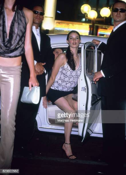 star getting off the car in company of two bodyguards - short skirts in cars stock photos and pictures