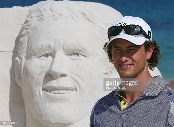 Star golfer Adam Scott of Australia poses next to his likeness created by sand sculpture Jenny Rossen during a photo shoot to launch the 2006 Johnnie...