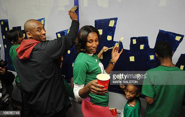 NBA star Kobe Bryant from the Los Angeles Lakers is helped by Lisa Leslie from the WNBA as they participate in the City Year School Refurbishment...