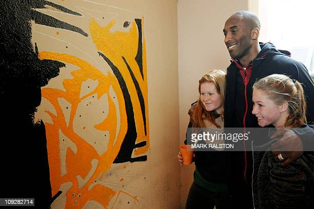 NBA star Kobe Bryant from the Los Angeles Lakers poses with students as he participates in the City Year School Refurbishment Project at the Virgil...