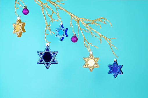 Star of David ornaments hanging from a gold branch - gettyimageskorea
