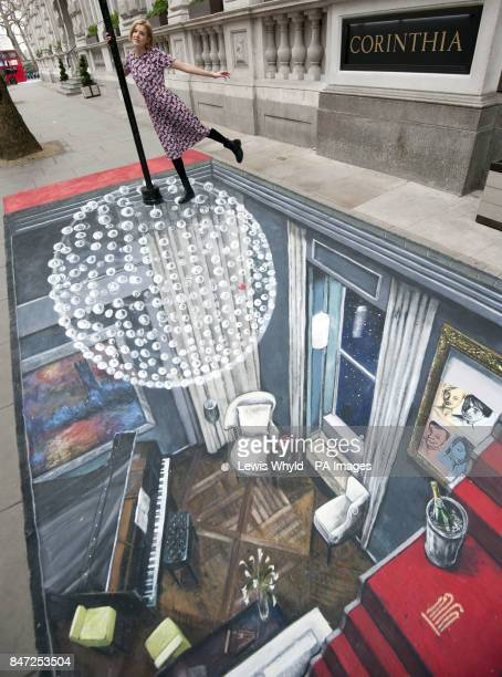 Star of The Leisure Society Agyness Deyn poses outside the Corinthia Hotel London on a piece of 3D Street Art created by Joe Hill who holds the...