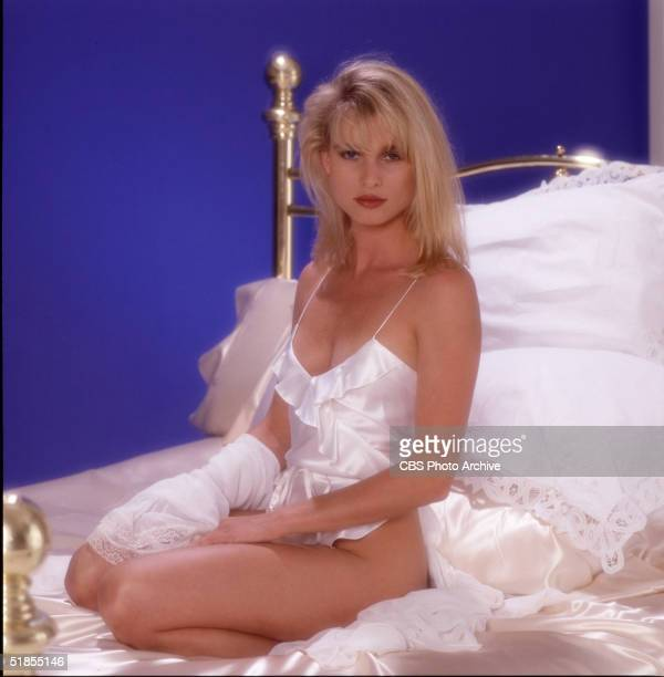 Star of the nighttime telvision soap opera 'Knots Landing' Englishborn American actress Nicolette Sheridan poses on a brass bed made with silk sheets...