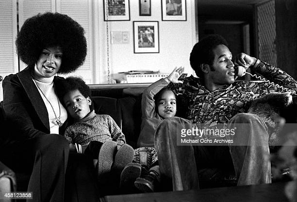 Star O.J. Simspson talks on the phone while doing a portrait session at home with his wife Marguerite Simpson, daughter Arnelle and son Jason on...