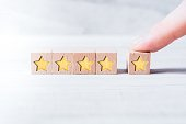 5 Star Ranking Formed By Wooden Blocks And Arranged By A Male Finger On A White Table