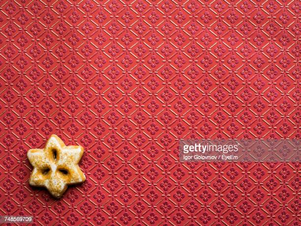 star shape gingerbread cookie on patterned maroon wall - igor golovniov stock pictures, royalty-free photos & images