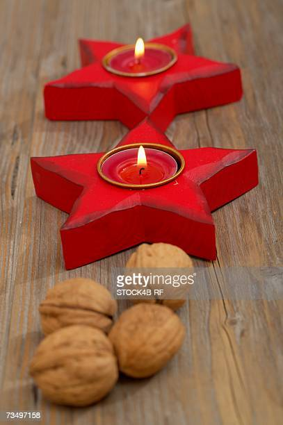 Star shaped candleholder with burning tea candles and walnuts
