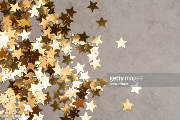 star shaped confetti on gray background. illuminating new year backdrop. - star shape stock pictures, royalty-free photos & images