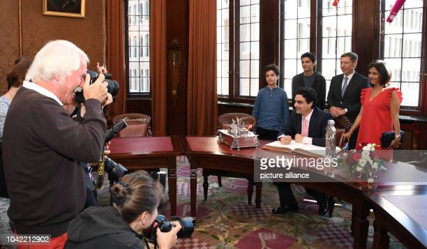 Star tenor Rolando Villazon signs the city's golden book in Bremen Germany 31 August 2016 In the background are his sons Matteo Dario mayor of Bremen...