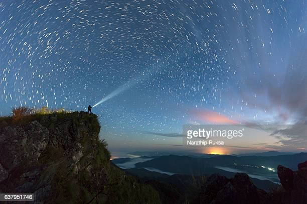 star trail over the mountain with the man light up the sky before sunsire, nan province, thailand - 北 ストックフォトと画像