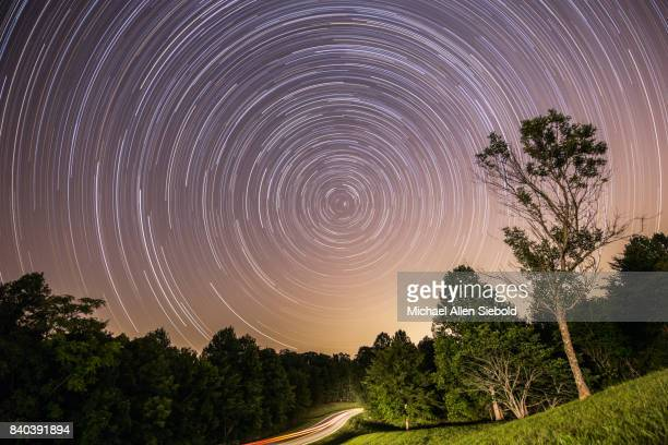star trail with headlight trail centered on polaris - concentric stock pictures, royalty-free photos & images