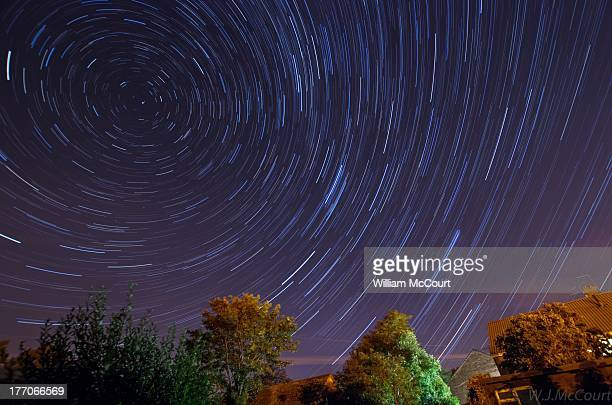 Star trails over a light polluted Sutton Courtenay . A meteor from the Perseid meteor shower is visible.