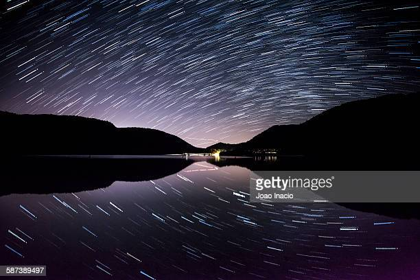 Star trails over calm lake, New Zealand