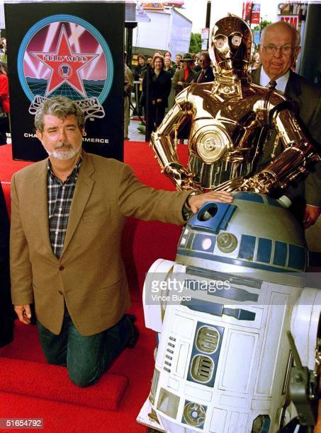 Star Wars creator George Lucas poses with Star Wars characters R2D2 and C3PO during a ceremony honoring special effects supervisor Dennis Muren who...