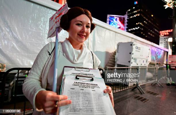 Star Wars fan Kristen Grady, dressed in costume as Princess Leia, holds a petition she is getting people to sign for Carrie Fisher, who played...