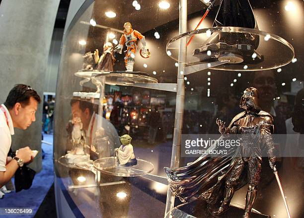 """Star Wars fan looks at figurines during the opening day of """"Star Wars Celebration IV"""" in Los Angeles, 24 May 2007. The five-day convention celebrates..."""