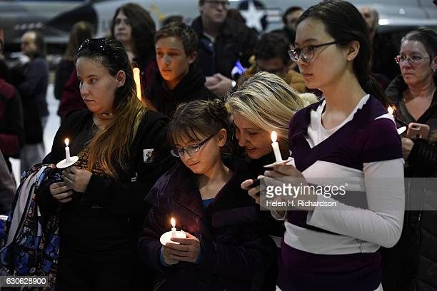 'Star Wars' fan Reyna Palmer middle and her mother Tonia second from right and other fans hold up candles and lightsabers during a vigil for actress...