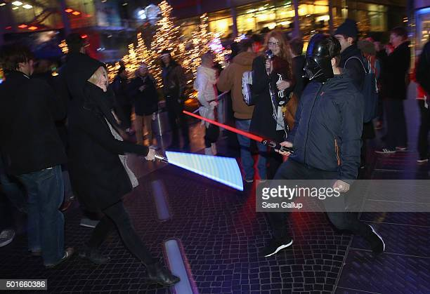 Star Wars fans battle with light sabers as they arrive for a midnight plus one minute first regular screening of 'Star Wars The Force Awakens' at the...