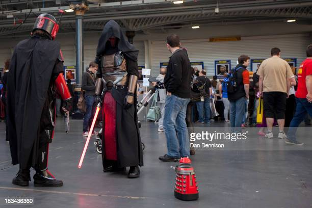 Star Wars fans confront a miniDalek at the London Film And Comic Con try on some hats at Olympia Exhibition Centre on October 6 2013 in London...