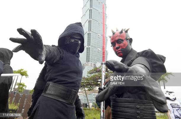 Star Wars fans dressed as Kylo Ren and Darth Maul pose for a photo in front of the Taipei 101 building in Taipei on May 4, 2019.