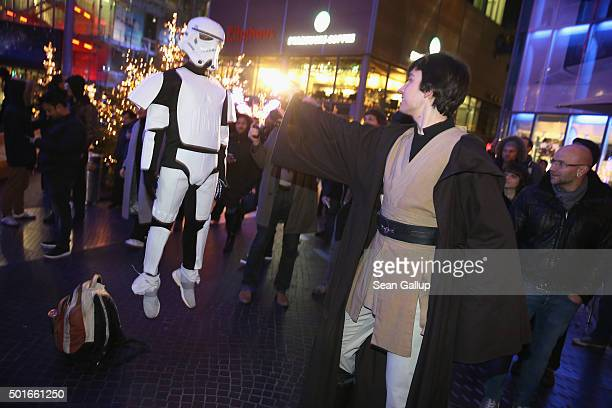 Star Wars fans dressed as Luke Skywalker and an Imperial Storm Trooper demonstrate The Force as they arrive for a midnight plus one minute first...