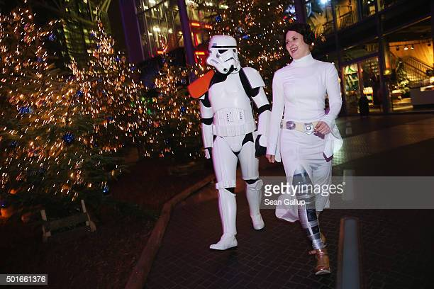 Star Wars fans dressed as Princess Leia and an Imperial Storm Trooper walk past Christmas lights they arrive for a midnight plus one minute first...