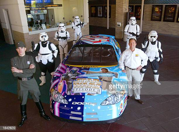 Star Wars fans dressed as stormtrooper characters stand next to the Star Warsschemed Cheerios No 43 Dodge Intrepid car commemorating the release of...