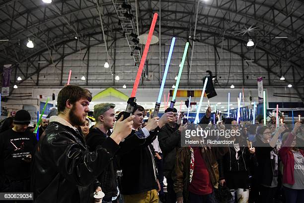 'Star Wars' fans of all ages hold up candles and lightsabers during a vigil for actress Carrie Fisher at the The Wings Over the Rockies Air and Space...