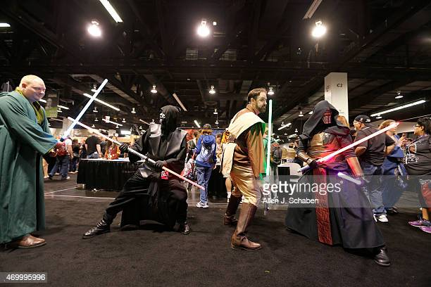 Star Wars fans pose with light sabers at the Star Wars Celebration at the Anaheim Convention Center on April 16 2015 in Anaheim California