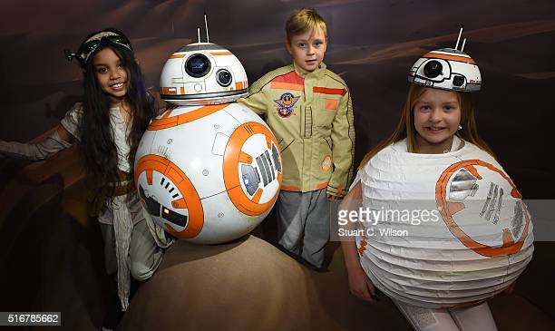 Star Wars fans pose with the new BB8 figure unveiled at Madame Tussauds London on March 21 2016 in London United Kingdom