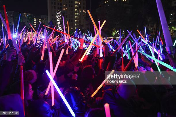 TOPSHOT Star Wars fans raise their lightsabers during Lightsaber Battle LA in Pershing Square in downtown Los Angeles California on December 18 2015...