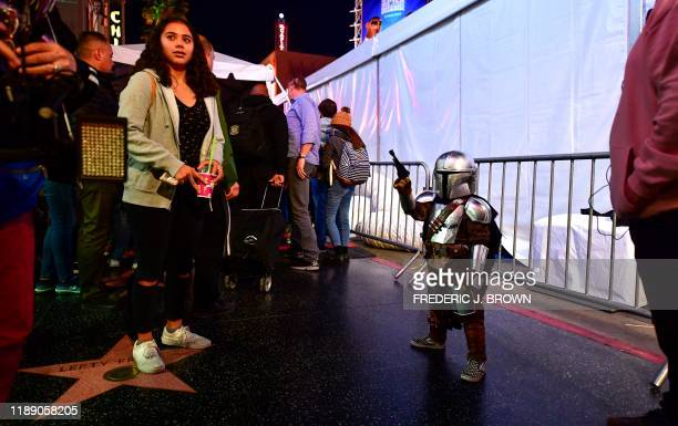 """Star Wars fans, some dressed in costume, hang around outside the world premiere of Disney's """"Star Wars: Rise of Skywalker"""" at the TCL Chinese Theatre..."""