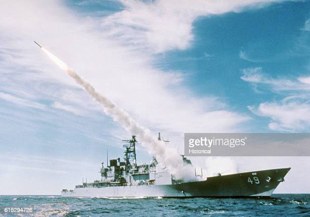 A starboard bow view of the Ticonderoga class Aegis guided missile cruiser Vincennes firing an RUR5A antisubmarine rocket from the forward Mark 26...