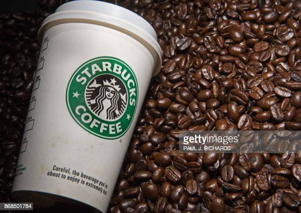 A Starbucks coffee cup and beans are seen in this photo taken August 12 2009 in Washington DC AFP Photo/Paul J Richards / AFP PHOTO / Paul J RICHARDS