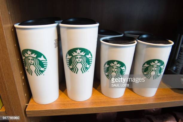 Starbucks coffee mugs are for sale inside a Starbucks Coffee shop in Washington DC April 17 following the company's announcement that they will close...