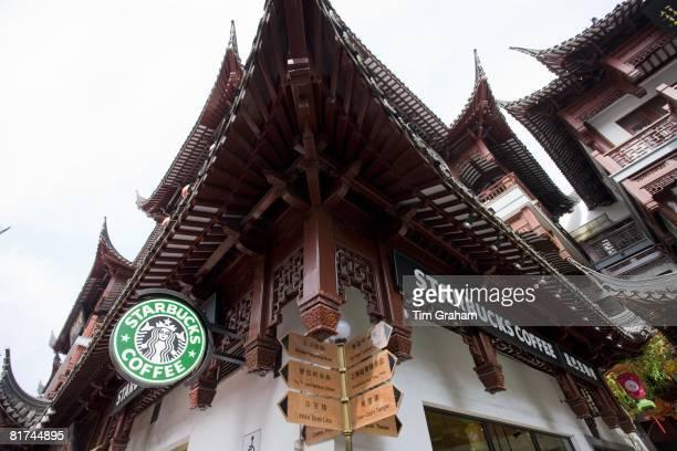 Starbucks coffee shop by Chinese streetsigns in the Yu Garden Bazaar Market Shanghai China