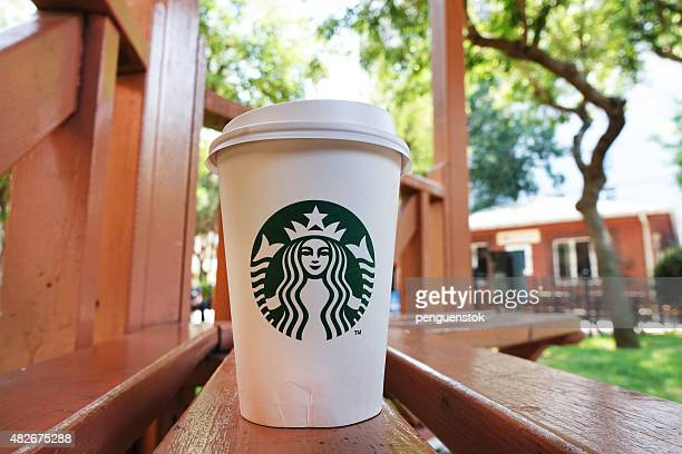 Starbucks Coffee to go paper cup with lid on bench