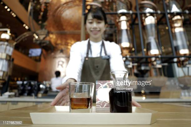 A Starbucks Corp employee displays a glass of whiskey barrelaged cold brew coffee during a media tour of the company's Reserve Roastery in Tokyo...