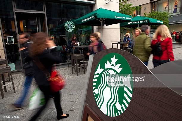 A Starbucks Corp logo sits on a board outside a coffee shop in Berlin Germany on Tuesday May 28 2013 Starbucks the world's biggest coffeeshop...