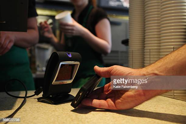 A Starbucks customer uses the Starbucks iPhone app to pay for a coffee at a store in Los Angeles